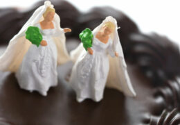 Tiny wedding figures atop a small heart-shaped pastry. These figures are extremely small, about half an inch tall. Very conceptual; Extremely shallow depth of field.